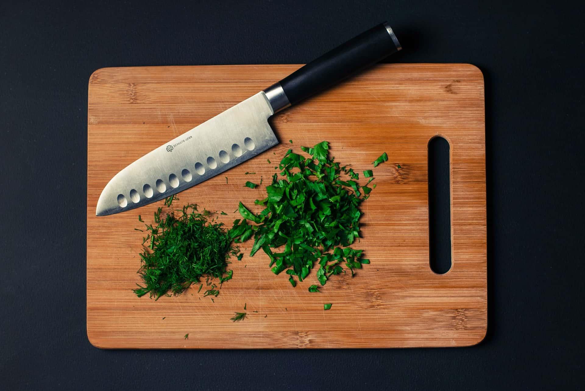 Tábua de madeira, com faca santoku, salsa e endro picados.