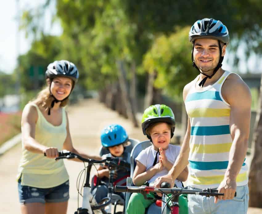 Imagem de uma mãe e de um pai usando capacete e segurando uma bicicleta cada um, onde os dois filhos estão sentados em uma cadeirinha.