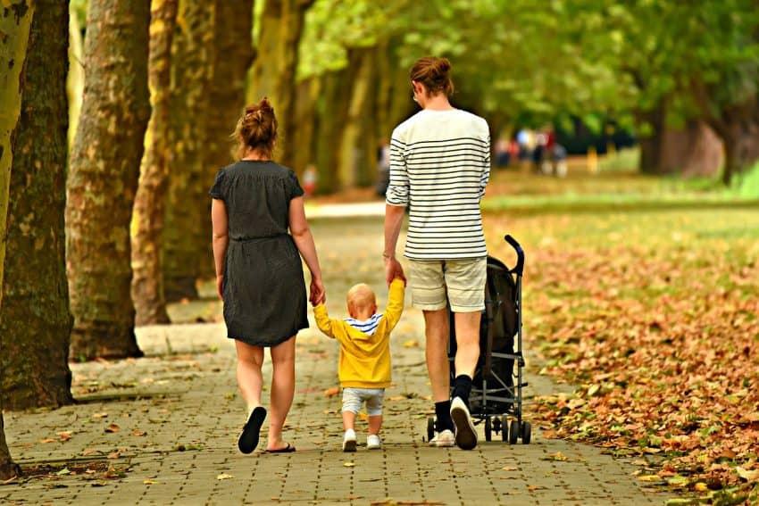 Imagem de uma família passeando em um parque e empurrando um carrinho de bebê.