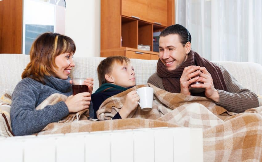 Imagem mostra aquecedor em primeiro plano, e ao fundo um homem e uma mulher com menino ao centro, sentados em um sofá com roupas de frio e cobertas enquanto tomam chocolate quente.
