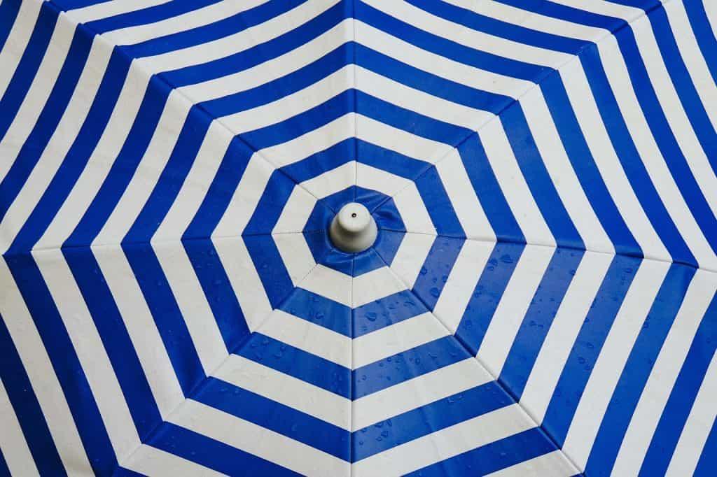Imagem mostra a cúpula de um guarda-sol listrada nas cores azul e branca