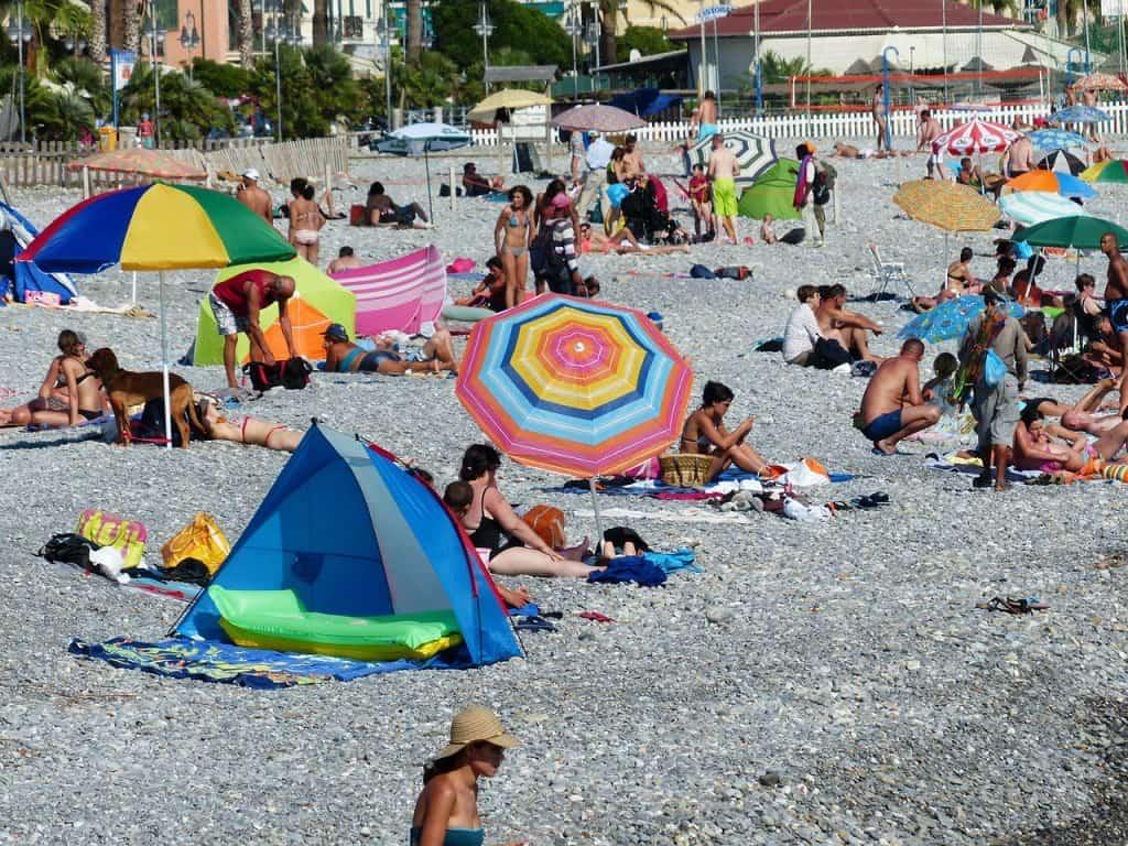 praia com diversas pessoas na faixa de areia usando guarda-sol