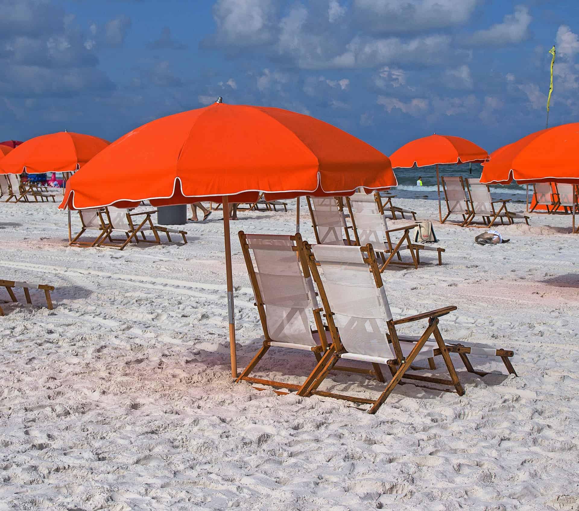 Imagem mostra um guarda-sol laranja com duas cadeiras de praia na areia