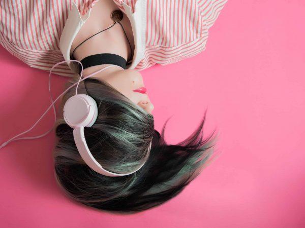 Mulher deitada com cabelo no rosto usando headsets.