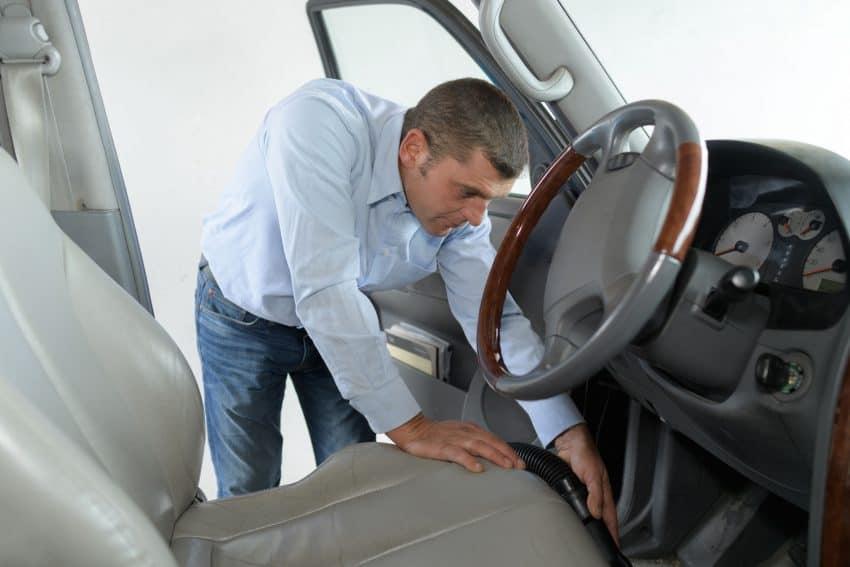 Homem utiliza aspirador de pó automotivo para limpar a parte interna de um carro.
