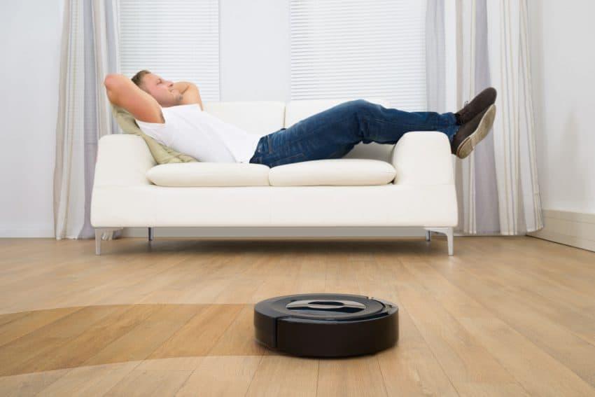 Homem deitado no sofá enquanto robô aspirador trabalha na sala.