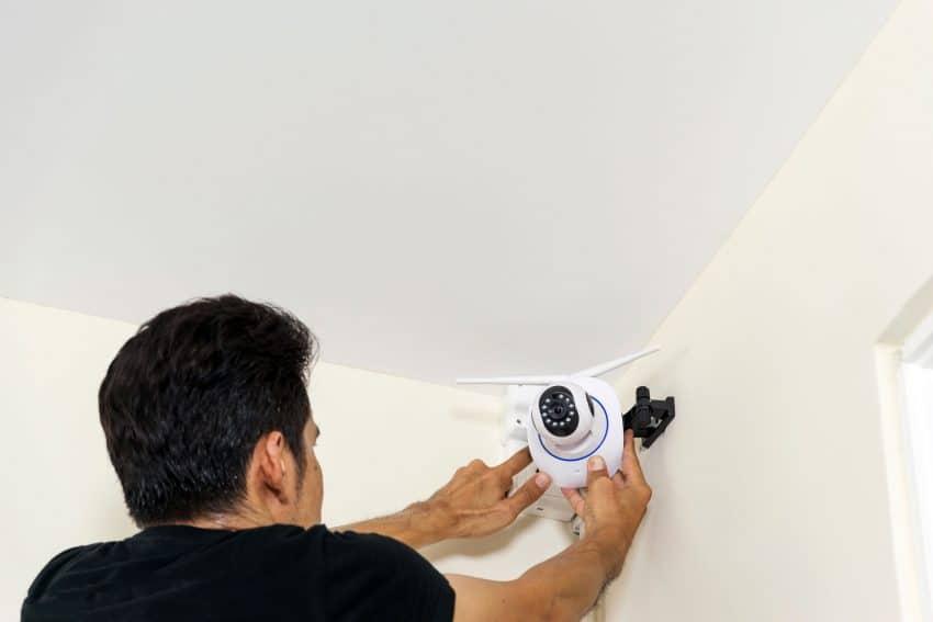 Homem instalando câmera ip.