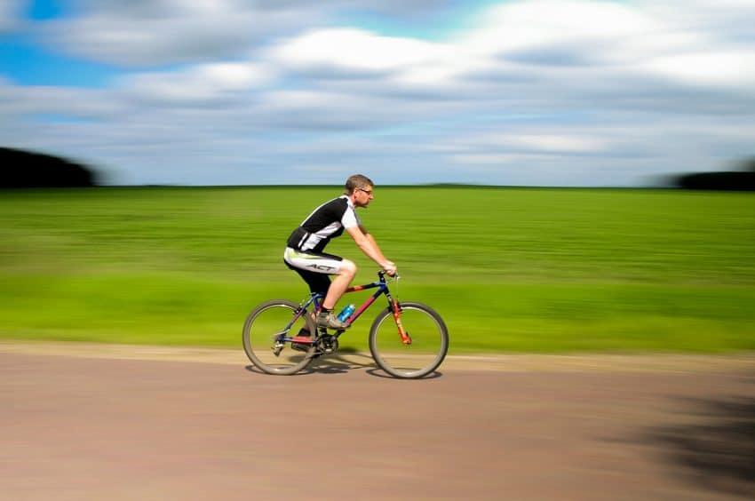 Homem pedalando em alta velocidade com fundo borrado.