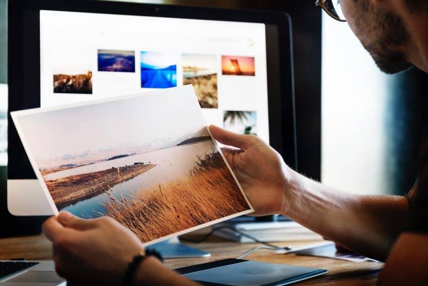Imagem de um homem com uma fotografia impressa na mão em frente à sua estação de trabalho.