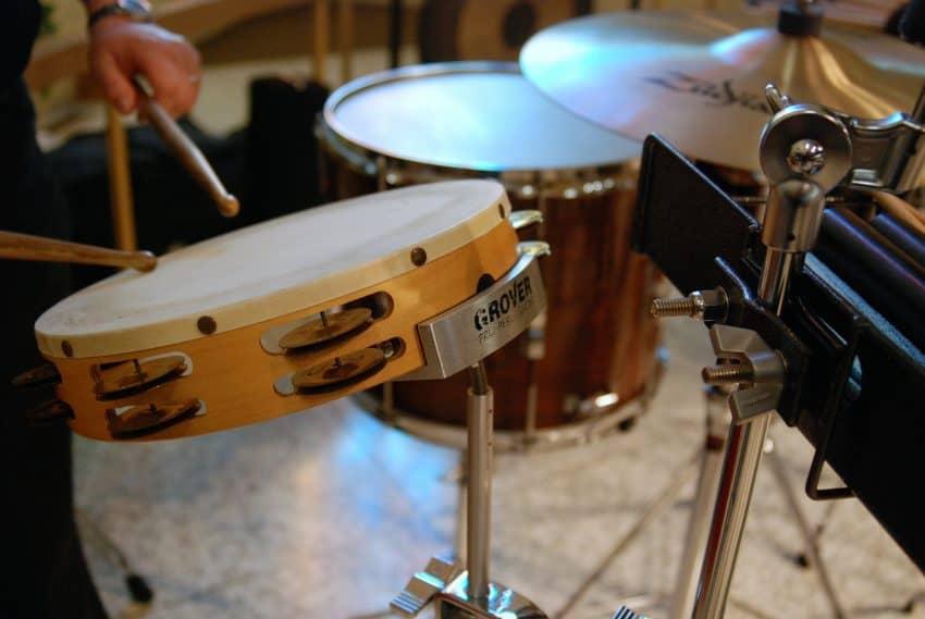 Pessoa em frente de vários instrumentos musicais. Em primeiro plano, um pandeiro.