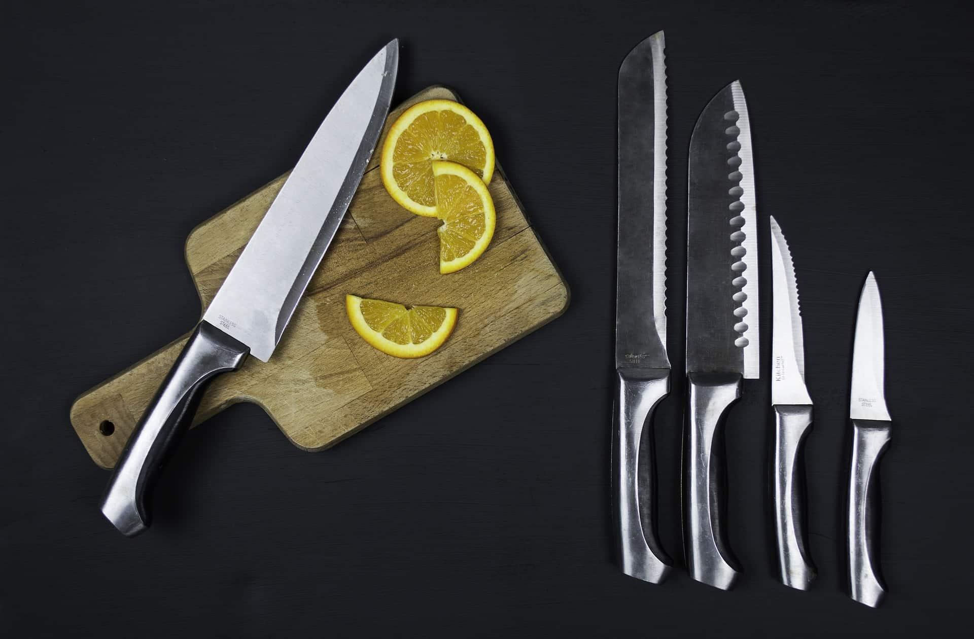 Imagem mostra 5 facas de inox, sendo que uma está em cima de uma tábua de madeira ao lado de um limão cortado.
