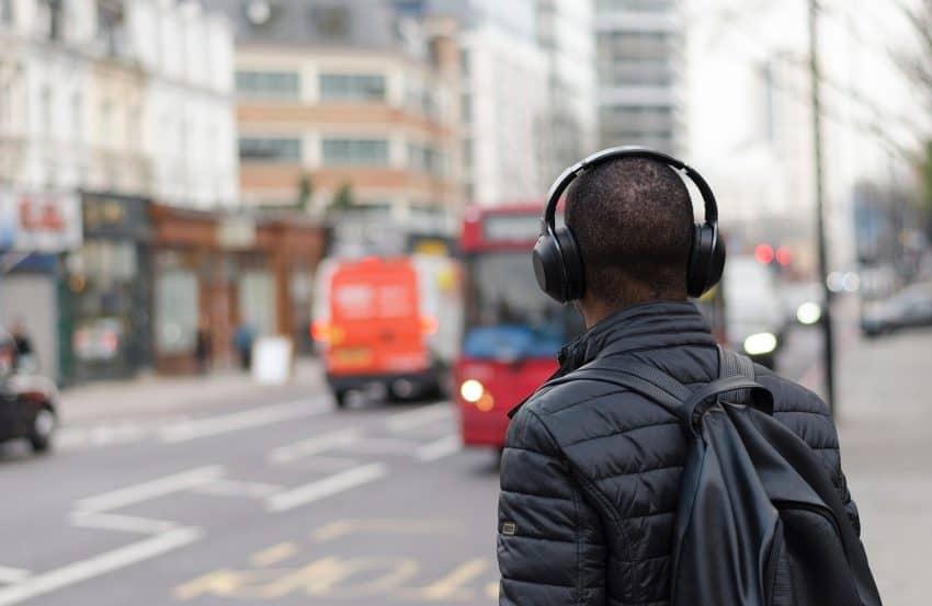 Jovem atravessando a rua com fone de ouvido e mochila nas costas.