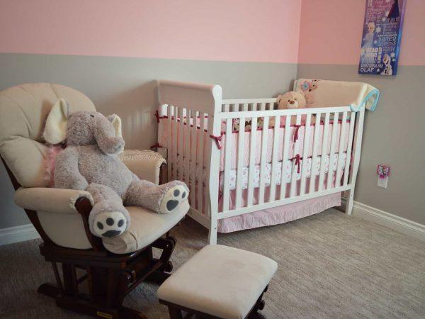 Quarto de bebê cinza e rosa, com poltrona e urso de pelúcia grande sobre ela, e berço branco decorado com kit berço.
