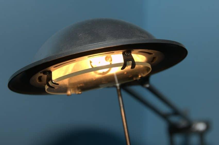 Imagem mostra um close na lâmpada amarela de uma luminária de luz direta.