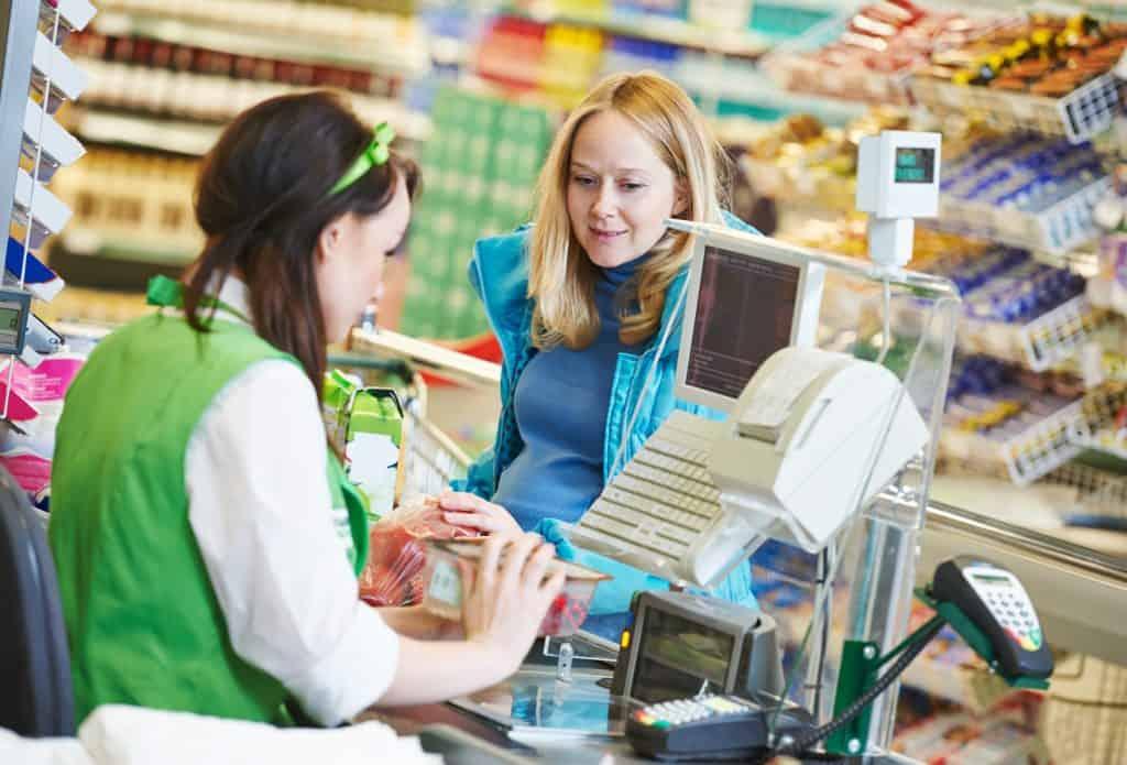 Mulher passando compra em caixa de supermercado, funcionária passando produto em leitor de código de barras.