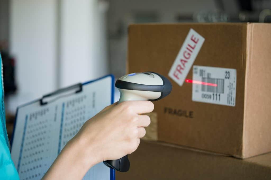 Mão usando um leitor de código de barras em uma caixa de papelão