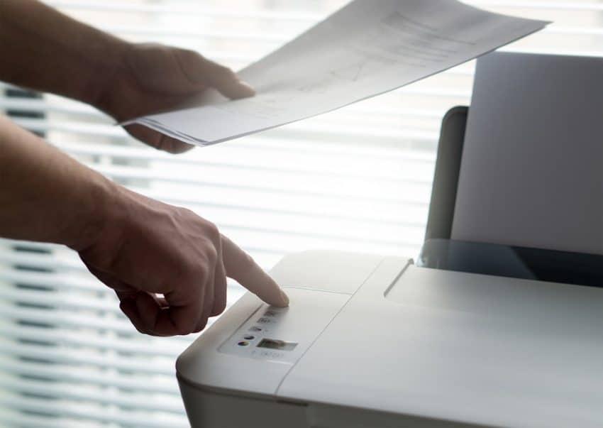 Imagem mostra uma pessoa segurando um papel em uma mão e apertando um botão da impressora com a outra.