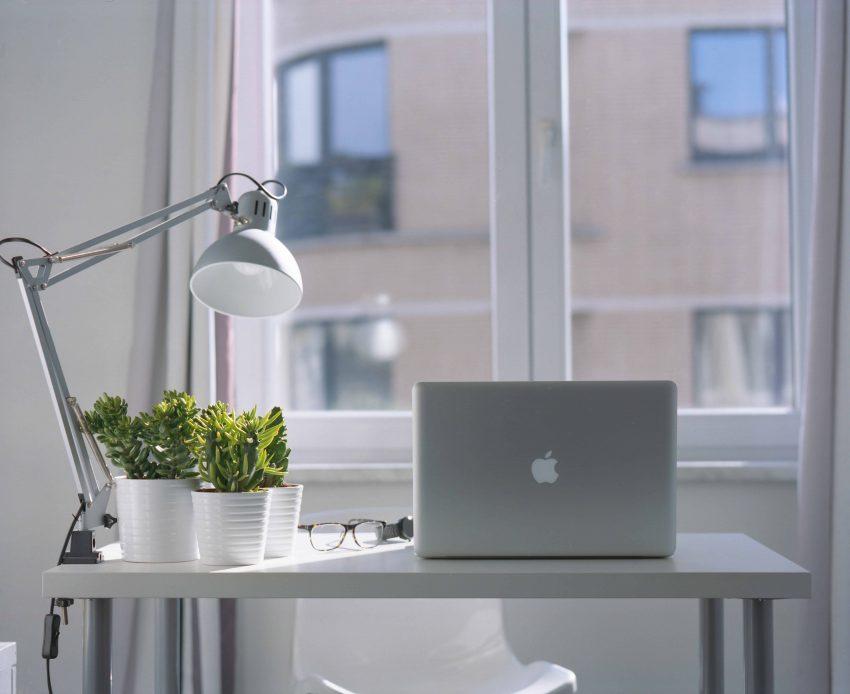 Imagem mostra uma pequena mesa, com uma luminária de luz direta do tipo Clip presa na sua extremidade esquerda. Na mesa, estão dispostos, três pequenos vasos de suculentas, um óculos e um notebook.