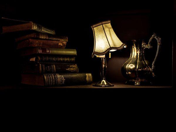 Imagem mostra uma luminária acesa ao centro, com uma pilha de livros ao seu lado esquerdo e um jarra ao lado direito.