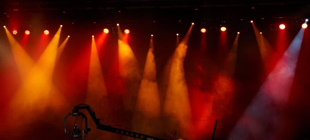Máquinas de fumaça em palco iluminado.
