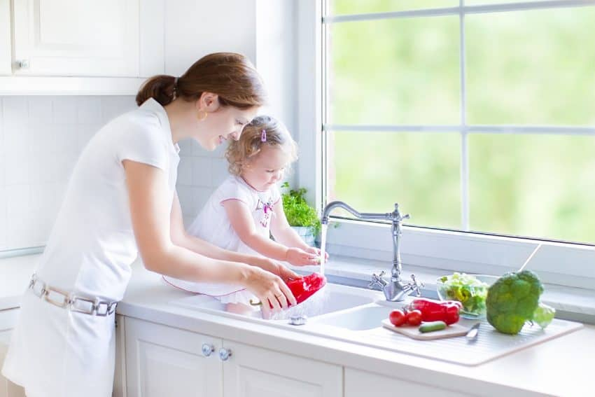 Mãe e filha lavando pimentão na pia da cozinha.