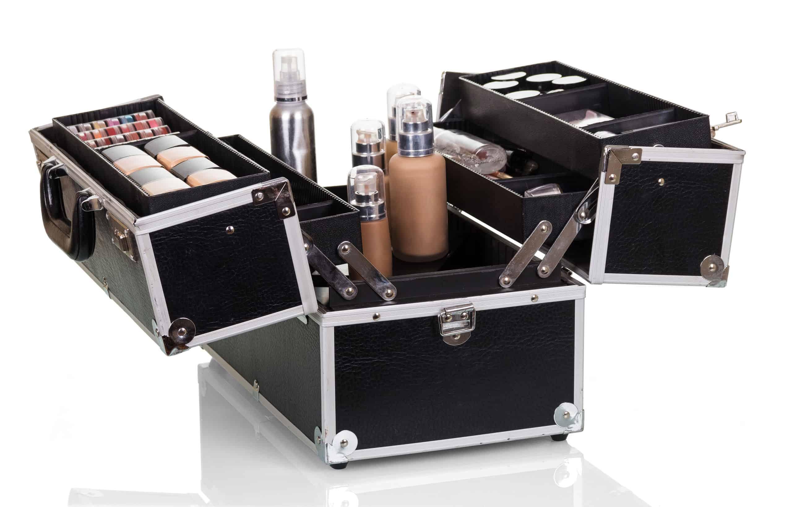 Na foto é possível ver uma maleta de maquiagem preta com detalhes em prata aberta e diversos itens de maquiagem expostos.