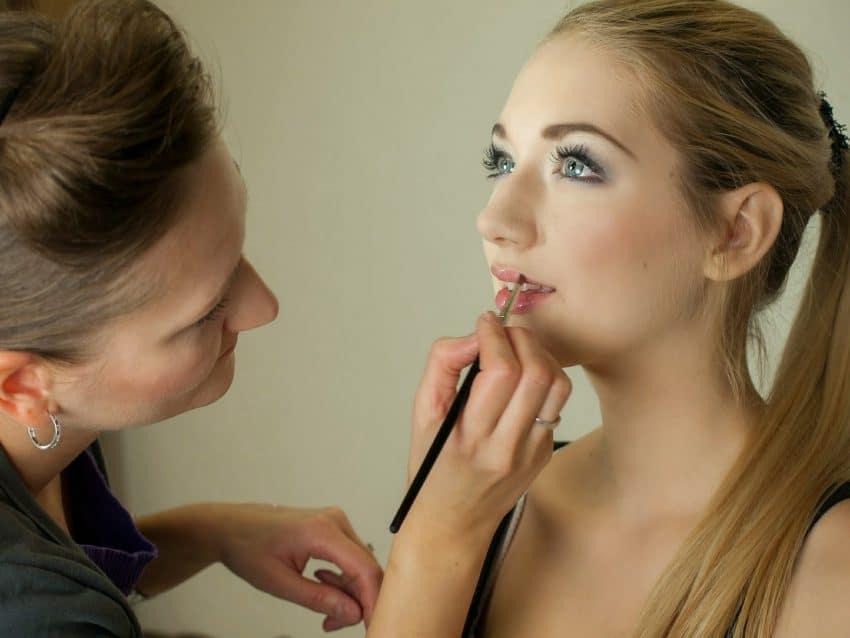 Na imagem é possível ver uma maquiadora, a esquerda, passando batom na boca de uma modelo, a direita, usando um pincel.
