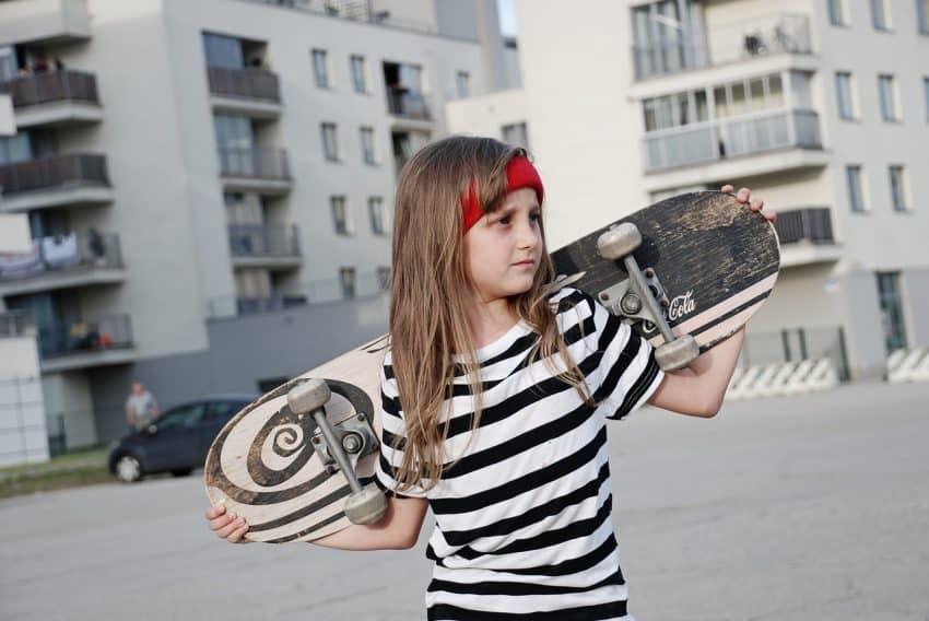 Imagem de uma menina segurando um skate.
