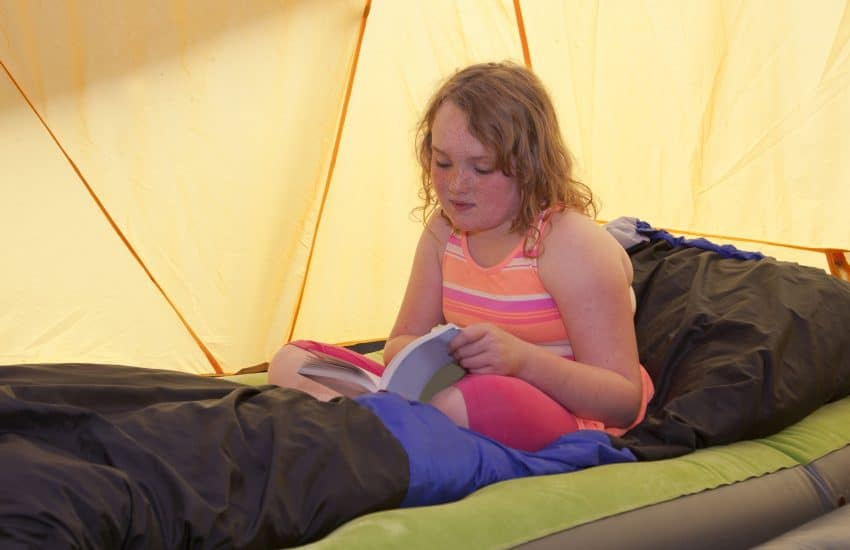 Menina lendo dentro da barraca.