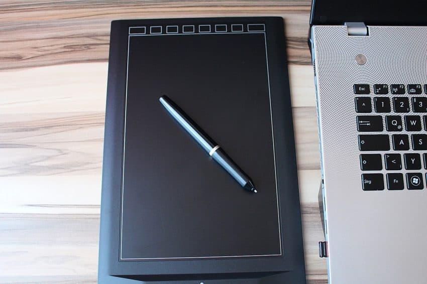 Imagem de uma mesa digitalizadora com a caneta em cima ao lado de um Macbook.