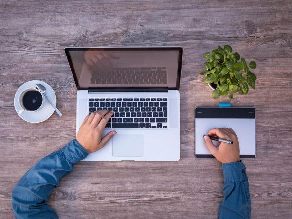 Imagem capturada de cima do uso de um Macbook e uma mesa digitalizadora.