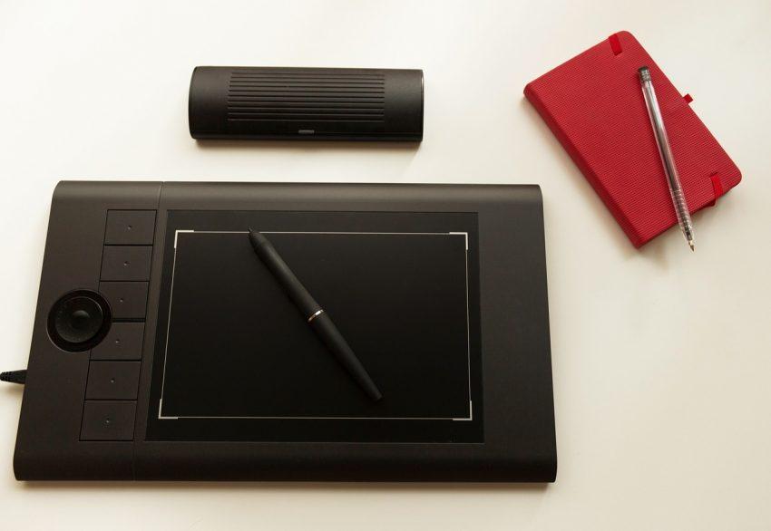 Imagem de uma mesa digitalizadora com sua caneta em cima e um bloco de notas ao lado.