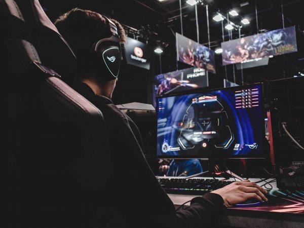 Imagem mostra um jogador em uma mesa segurando um mouse gamer e utilizando headset gamer
