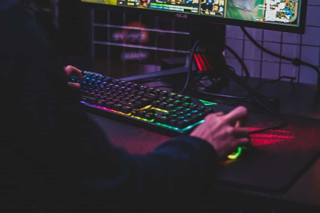 Imagem mostra um teclado e mouse gamer sobre uma mesa