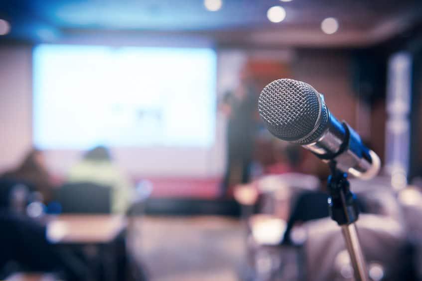 Microfone sem fio no pedestal em primeiro plano com sala borrada ao fundo.