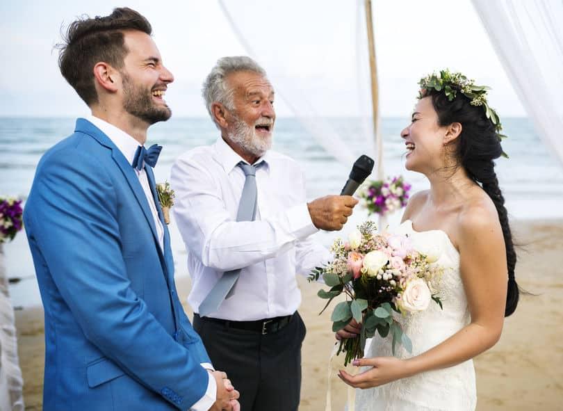 casal casando na praia, noiva está rindo perto de um celebrando que segura um microfone sem fio