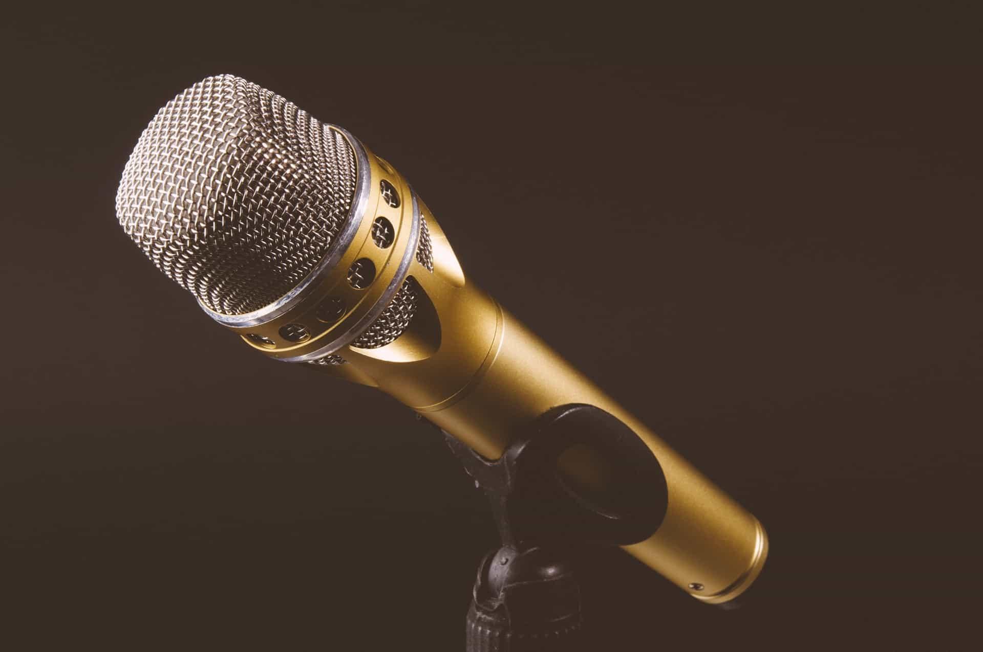 Fundo escuro com um microfone dourado de metal.