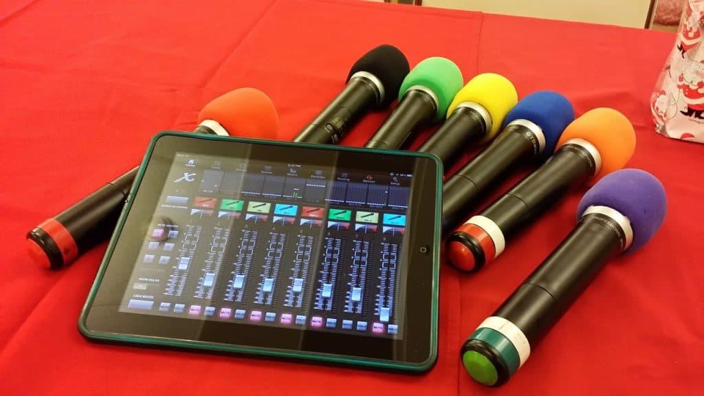 7 microfones com capinhas coloridas em cima de um edredom vermelho. Em cima deles, há um tablet com um programa de música aberto.