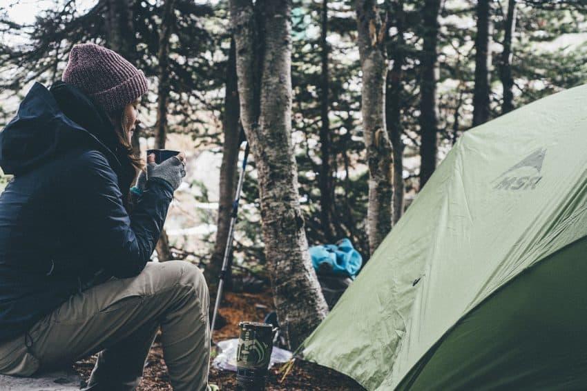 Uma mulher relaxa enquanto toma uma xícara de café sentada em uma pedra ao lado da barraca de camping.