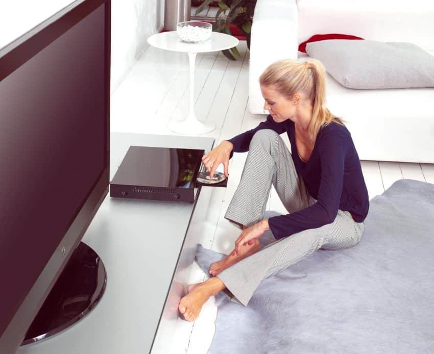 Mulher sentada no chão colocando o dvd no aparelho.