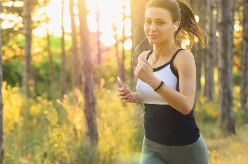 Mulher com fone de ouvidos e roupa de ginástica pratica corrida ao ar livre em uma paisagem com bastante contato com a natureza.