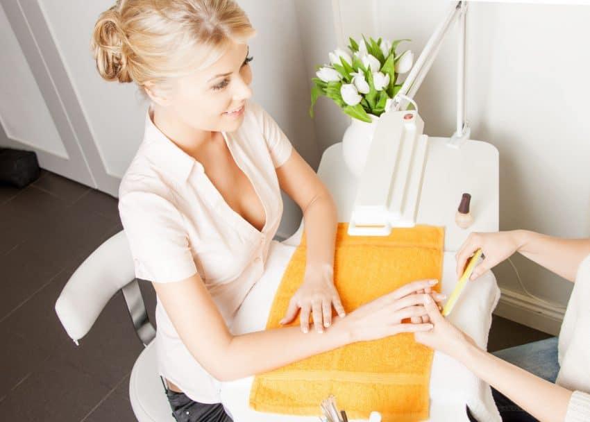 Mulher fazendo a unha com uma manicure.