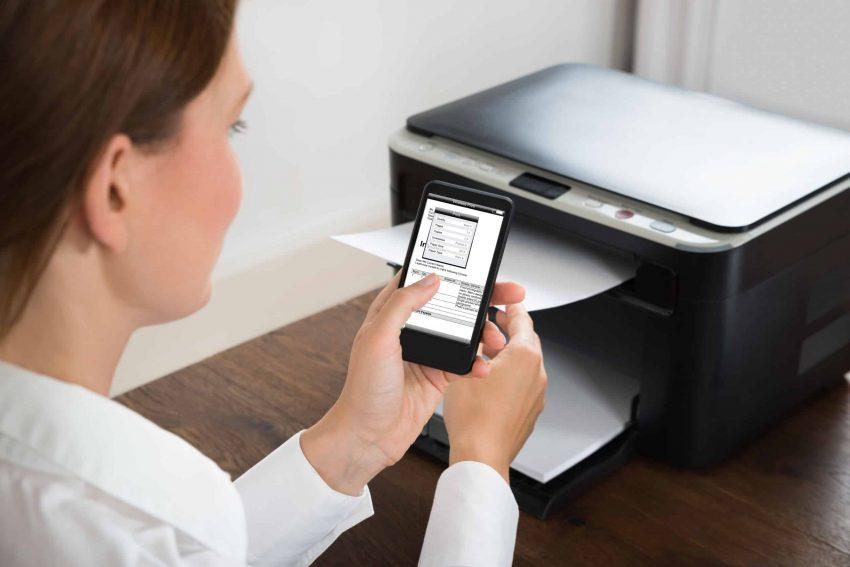 Imagem mostra mulher em frente a uma impressora enviando documento para imprimir pelo celular.