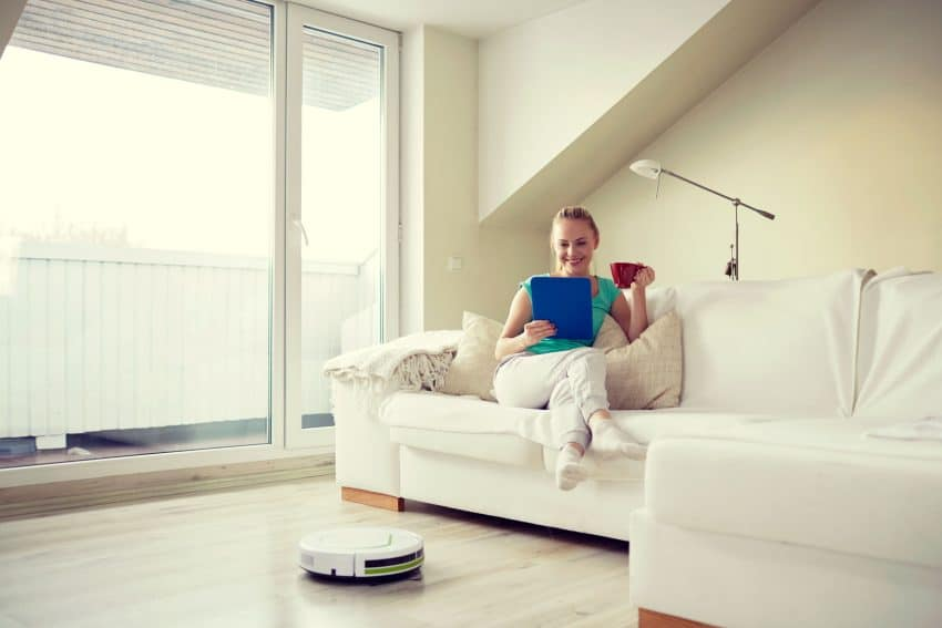 Mulher sentada no sofá lendo e tomando uma bebida enquanto robô aspirador trabalha.