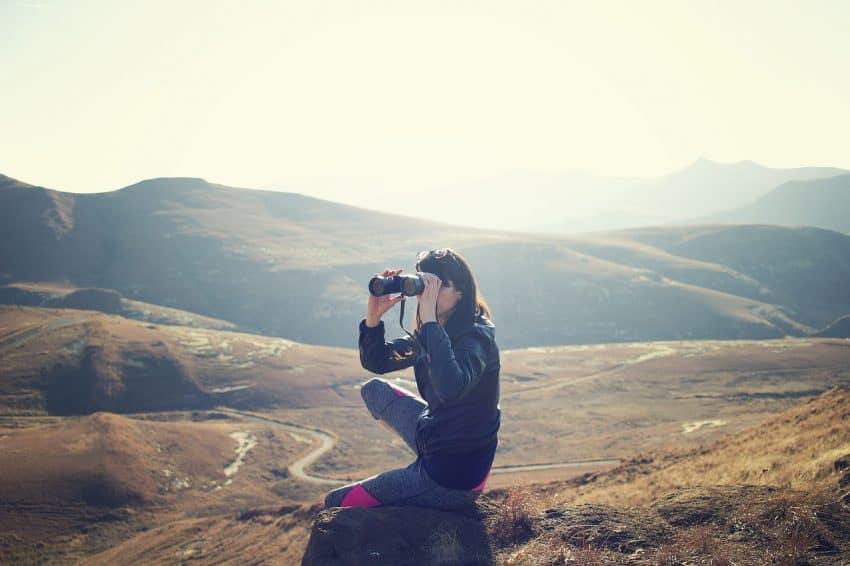Mulher sentada no chão observando lugar deserto através de um binóculo.