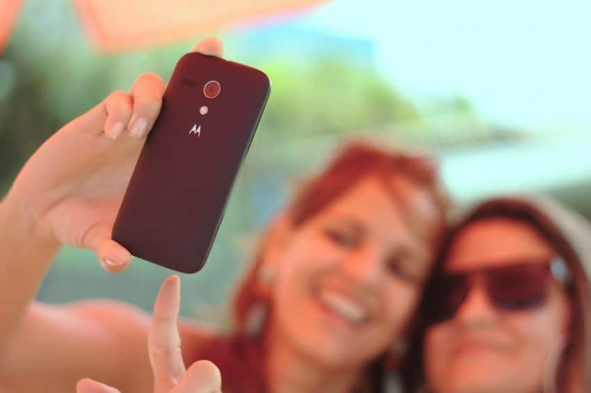 Duas mulheres fazendo selfie com um celular preto.