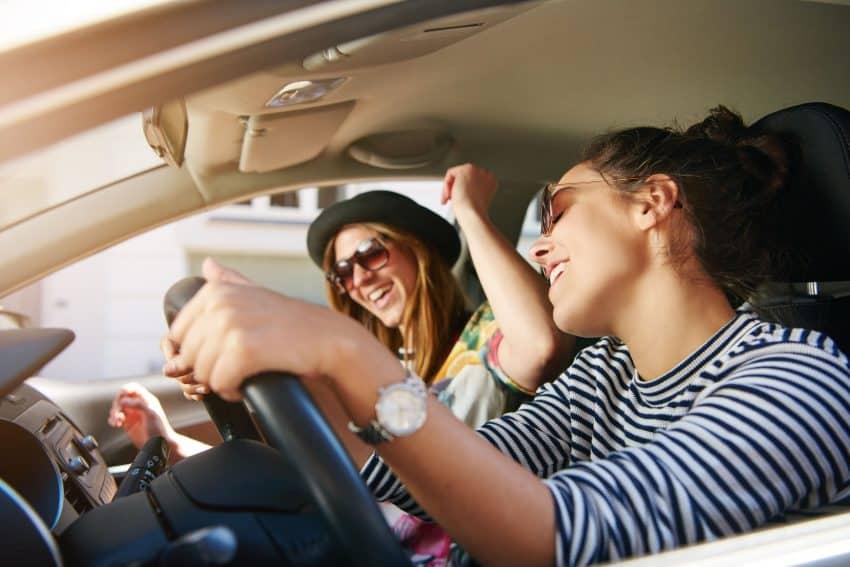 Meninas ouvindo música e dançando no carro.