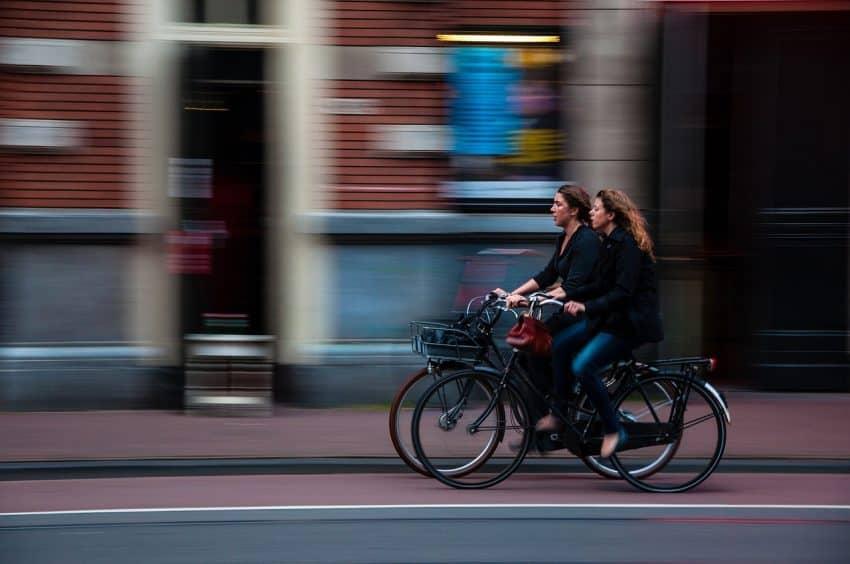 Duas garotas pedalando na ciclofaixa da cidade.