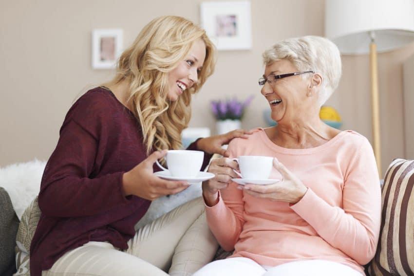 Duas mulheres sorrindo e bebendo café em casa sentadas no sofá.