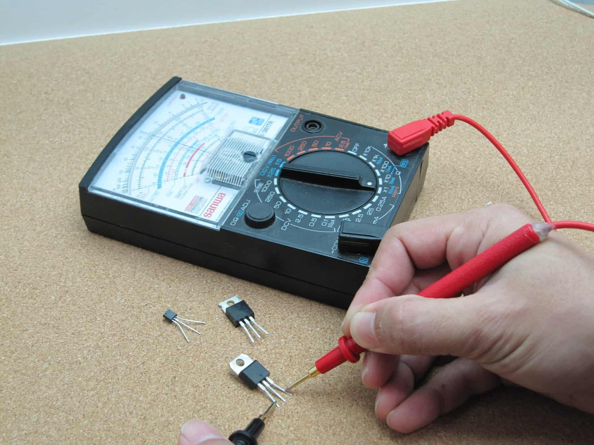 Foto de um multímetro em uso, utilizando as pontas de prova para realizar medição num transistor.
